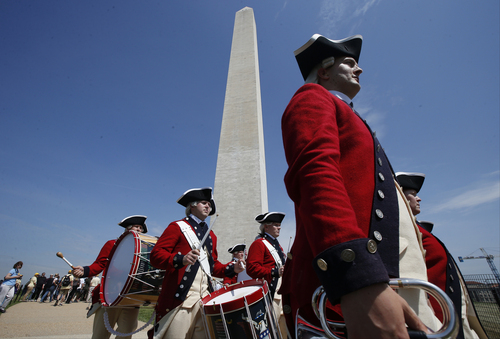 Members of the United States Army Old Guard Fife and Drums Corps march beneath the Washington Monument in Washington, Monday, May 12, 2014, during a ceremony to celebrate its re-opening. The monument, which sustained damage from an earthquake in August 2011, reopened to the public today. (AP Photo)