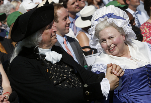 George Washington played by Dean Malissa, left, and Martha Washington played by Mary Wiseman, attend a ceremony to celebrate the re-opening of the Washington Monument, Monday, May 12, 2014, in Washington. The monument, which sustained damage from an earthquake in August 2011, reopened to the public today. (AP Photo)