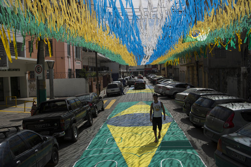 A man walks along a street decorated for the upcoming World Cup in Rio de Janeiro, Brazil, Wednesday, May 14, 2014. The international soccer tournament will be the first in the South American nation since 1950. (AP Photo/Felipe Dana)