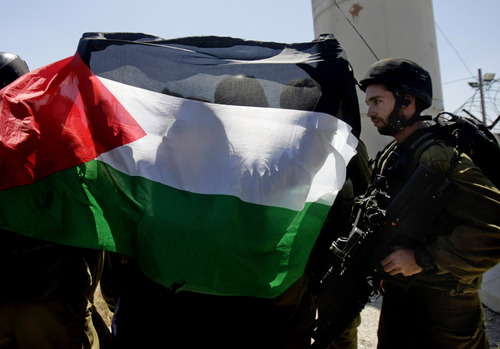 """Palestinians hold a national flag during a rally marking the 66th anniversary of what the Palestinians call the """"Nakba,"""" or """"catastrophe"""" referring to their uprooting in the war over Israel's 1948 creation, as an Israeli soldiers stand guard at Hawara checkpoint near the West Bank city of Nablus, Wednesday, May 14, 2014. According to the U.N. figures, more than 700,000 Palestinians fled or were driven out in the 1948 Mideast war, many settling in the West Bank, Gaza, Jordan, Lebanon and Syria. (AP Photo/Nasser Ishtayeh)"""