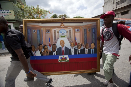 Supporters of Haiti's President Michel Martelly carry a painting where Martelly, center, is flanked by former Haitian presidents during an event to mark his three years in power in Port-au-Prince, Haiti, Wednesday, May 14, 2014. A couple thousand people protested in Haiti's capital as they marked the third anniversary of Michel Martelly's presidency and called for his departure. The protesters tried to reach the area near the National Palace where Martelly was commemorating the anniversary with a street party of his own, but they were turned away by police barricades and riot-control officers who used tear gas to disperse them. ( AP Photo/Dieu Nalio Chery)