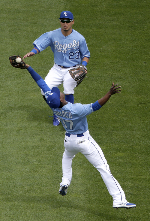 Kansas City Royals second baseman Pedro Ciriaco (37) has the ball bounce from his glove on a double by Colorado Rockies' Nolan Arenado as right fielder Norichika Aoki watches during the seventh inning of a baseball game Wednesday, May 14, 2014, in Kansas City, Mo. (AP Photo/Charlie Riedel)