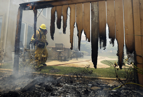 A Firefighter puts water on a house fence during a wildfire Wednesday, May 14, 2014, in Carlsbad, Calif. More wildfires broke out Wednesday in San Diego County — threatening homes in Carlsbad and forcing the evacuations of military housing and an elementary school at Camp Pendleton — as Southern California is in the grip of a heat wave. (AP Photo)