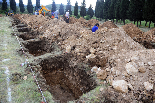 The rows of open tenantless graves are prepared for the mine accident victims in Soma, Turkey, Wednesday, May 14, 2014.   Nearly 450 miners were rescued, the mining company said, but the fate of an unknown number of others remained unclear as bodies are still being brought to the surface and burials are underway after one of the world's deadliest mining disasters. (AP Photo/Emre Tazegul)