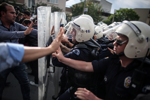 """Riot police try to stop protesters who were attacking the offices of Prime Minister Recep Tayyip Erdogan's Justice and Development Party, in Soma, Turkey, during his visit to the coal mine in Soma Wednesday, May 14, 2014.  A violent protest erupted Wednesday in the Turkish city of Soma, where at least 238 coal miners have died after a mine explosion as many in the crowd expressed anger at Prime Minister Recep Tayyip Erdogan's government, rocks were thrown and some people were shouting that Erdogan was a """"Murderer!"""" and a """"Thief!""""(AP Photo/Emrah Gurel)"""