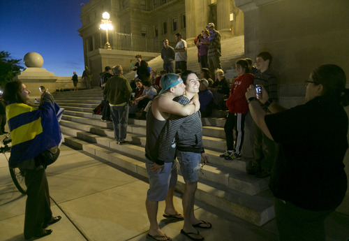 Mike Chase, center left, kisses his partner Matthew Montoya on the steps of the Idaho Statehouse during a rally in support of same sex marriage in Boise on Tuesday night May 13, 2014. U.S. Magistrate Judge Candy Dale ruled earlier in the day that Idaho's ban on gay marriage is unconstitutional. (AP Photo/The Idaho Statesman, Kyle Green)