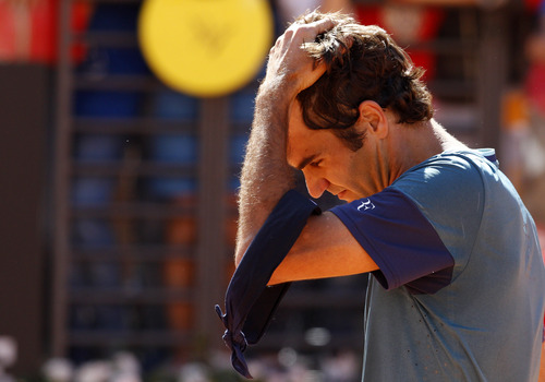 Switzerland's Roger Federer reacts after being defeated by France's Jeremy Chardy at the Italian open tennis tournament in Rome, Wednesday, May 14, 2014. Roger Federer appeared to lose focus in his first match back after the birth of his second set of twins, losing to 47th-ranked Jeremy Chardy of France 1-6, 6-3, 7-6 (6) in the second round of the Italian Open on Wednesday. (AP Photo/Riccardo De Luca)