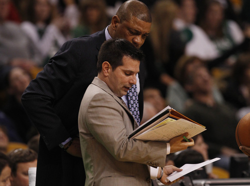 Boston Celtics head coach Doc Rivers tlooks over the shoulder of assistant coach  Mike Longabardi during the second half of an NBA basketball game in Boston, Friday, Jan. 4, 2013. The Celtics beat the Pacers 94-75. (AP Photo/Charles Krupa)