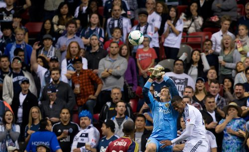 Real Salt Lake goalkeeper Jeff Attinella, left, makes the save as Vancouver Whitecaps' Carlyle Mitchell, of Trinidad & Tobago, tries to get his head on the ball during the second half of an MLS soccer game Saturday, Sept. 28, 2013, in Vancouver, British Columbia. (AP Photo/The Canadian Press, Darryl Dyck)