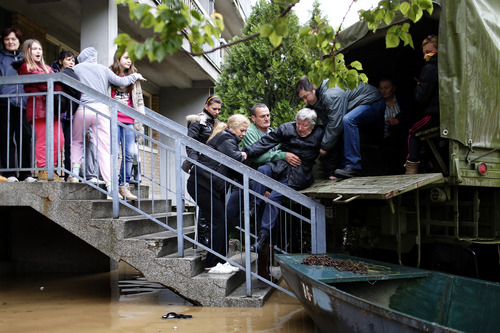 A woman is evacuated from her home in Obrenovac, some 30 kilometers (18 miles) southwest of Belgrade, Serbia, Friday, May 16, 2014. Serbian authorities are considering full evacuation of Obrenovac, inhabited by roughly 25 thousand people, as the local rivers have flooded the vast majority of the town's residential areas. (AP Photo/Marko Drobnjakovic)