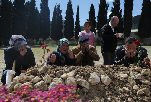 Family members pray at the grave of a victim from the mine accident, in Soma, Turkey, Friday, May 16, 2014. A Turkish mining company defended its safety record Friday, four days after over 250 people died in an underground blaze at its coal mine in western Turkey. (AP Photo/Emre Tazegul)