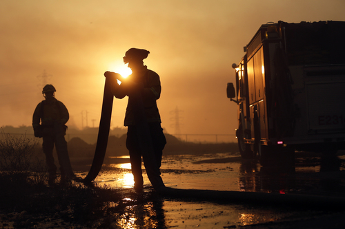 Del Mar firefighters roll up hose after a day fighting wildfires Wednesday, May 14, 2014, in Carlsbad, Calif. More wildfires broke out Wednesday in San Diego County,  threatening homes in Carlsbad and forcing the evacuations of military housing and an elementary school at Camp Pendleton. (AP Photo)