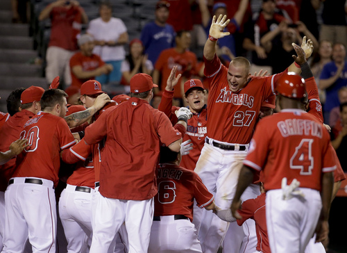 Los Angeles Angels' Mike Trout, (27), celebrates his three-run walk off home run against the Tampa Bay Rays on during the ninth inning of a baseball game in Anaheim, Calif., Thursday, May 15, 2014. (AP Photo/Chris Carlson)
