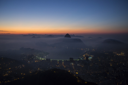 Sugarloaf Mountain and the Guanabara Bay are seen in a blanket of early morning fog as the sun begins to rise in Rio de Janeiro, Brazil, Friday, May 16, 2014. As opening day for the World Cup approaches, people continue to stage protests, some about the billions of dollars spent on the World Cup at a time of social hardship, but soccer is still a unifying force. The international soccer tournament will be the first in the South American nation since 1950. (AP Photo/Felipe Dana)