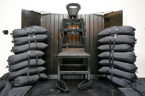 Trent Nelson  |  Tribune file photo  The execution chamber at the Utah State Prison after Ronnie Lee Gardner was executed by firing squad Friday, June 18, 2010. Four bullet holes are visible in the wood panel behind the chair. Gardner was convicted of aggravated murder, a capital felony, in 1985.