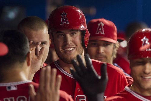 Los Angeles Angels' C.J. Cron, center, is congratulated in the dug out after scoring on a two-run home run by Chris Iannetta during second inning  of a baseball game against the Toronto Blue Jays in Toronto on Saturday, May 10, 2014. (AP photo/The Canadian Press, Chris Young)
