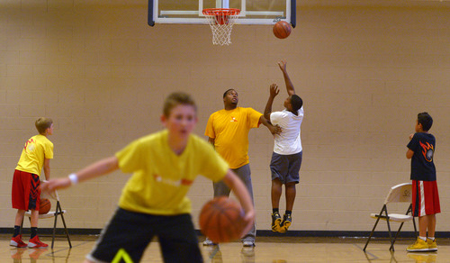Leah Hogsten  |  The Salt Lake Tribune Former Utah Jazz center Robert Whaley provides defense under the net for his son, Robert, 11, during practice. Whaley directs young basketball players as coach of Utah Elite, Tuesday, May 13, 2014. Whaley played in 23 games for the Jazz during the 2005-06 season.