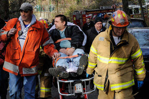 """FILE - In this Dec. 1, 2013 photo, Metro North Railroad engineer William Rockefeller is wheeled on a stretcher away from the area where the commuter train he was operating derailed, killing four people, in the Bronx borough of New York. The deadly derailment last year, in which the """"dazed"""" engineer was found to have sleep apnea, has pushed the commuter railroad to look into establishing screening for the condition, which could include measuring operators' necks and asking them and their spouses about snoring habits. A Metro-North spokesman confirmed the railroad that serves New York City's northern suburbs is working with unions on sleep apnea screening, but he cautioned nothing has been decided.(AP Photo/Robert Stolarik, File)"""
