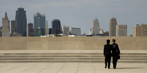 In this April 23, 2014 photo, transgender high school students Isaac Barnett, left, and his prom date, identified only by his first name Jasen, look at the Kansas City, Mo. skyline after picking up their tuxedos for prom Wednesday, April 23, 2014.  The seniors, both born as females, are open about their transgender status in their schools and say friends, teachers and administrators have been much more supportive than they expected. (AP Photo/Charlie Riedel)