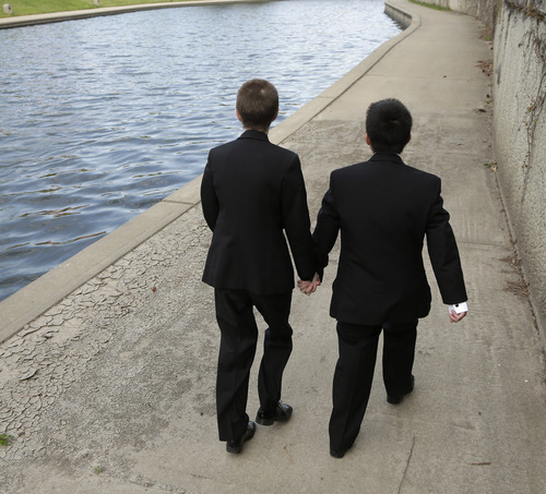 In this April 23, 2014 photo, transgender high school students Isaac Barnett, right, and his prom date, identified only by his first name Jasen, walk along a creek in the Country Club Plaza shopping district after picking up their tuxedos for prom in Kansas City, Mo. The seniors, both born as females, are open about their transgender status in their schools and say friends, teachers and administrators have been much more supportive than they expected. (AP Photo/Charlie Riedel)
