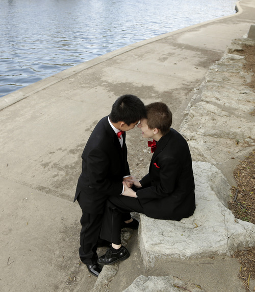 In this April 23, 2014 photo,transgender high school students Isaac Barnett, left, and his prom date, identified only by his first name Jasen, relax along a creek in the Country Club Plaza shopping district after picking up their tuxedos for prom. The seniors, both born as females, are open about their transgender status in their schools and say friends, teachers and administrators have been much more supportive than they expected. (AP Photo/Charlie Riedel)