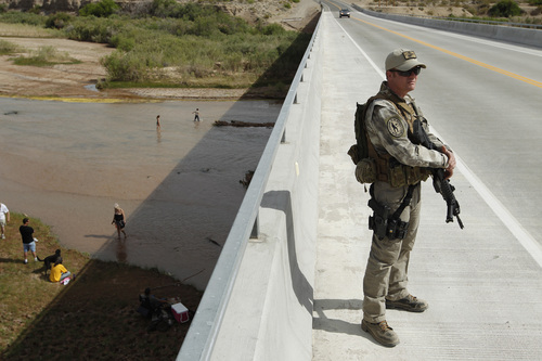 Justin Giles of Wasilla, Alaska stands guard on a bridge over the Virgin River during a rally in support of Cliven Bundy near Bunkerville, Nev. Friday, April 18, 2014. (AP Photo/Las Vegas Review-Journal, John Locher)
