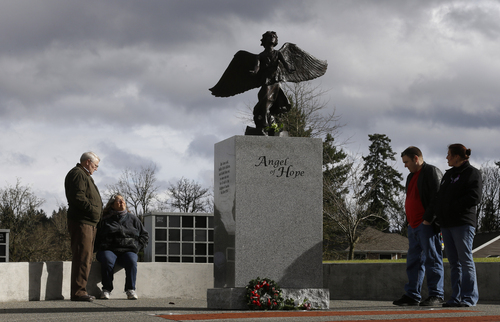 Chuck  and Judy Cox, left, the parents of missing Utah mother Susan Cox Powell, are joined by Susan's sister Denise Cox, right, and her fiancé, Andrew Olsen, second from right, at statue of an angel, Tuesday, Feb. 5, 2013, at Woodbine Cemetery in Puyallup, Wash., where Susan's sons Charlie and Braden Powell are buried. Charlie and Braden were killed on Feb. 5, 2012, by their father, Josh Powell, who also killed himself. Powell was a suspect in the disappearance of his wife Susan Cox Powell in 2009 in Utah. (AP Photo/Ted S. Warren)