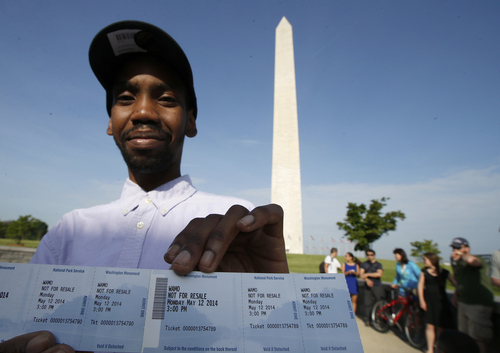 Visitor Roman Tanner displays his Washington Monument ticket, which are distributed at on a first-come basis at the Washington Monument in Washington, Monday, May 12, 2014, ahead of a ceremony to celebrate its re-opening. The monument, which sustained damage from an earthquake in August 2011, is reopening to the public today. (AP Photo)