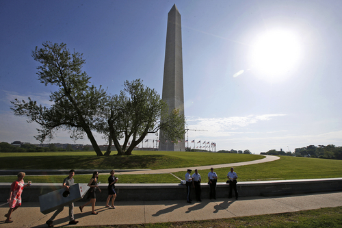 Steven Avila, a Department of Interior employee, left, carries a Washington Monument costume as he arrives at the Washington Monument in Washington, Monday, May 12, 2014, ahead of a ceremony to celebrate its re-opening. The monument, which sustained damage from an earthquake in August 2011, is reopening to the public today. Avila made the costume to show his support for the re-opening of the monument. (AP Photo)