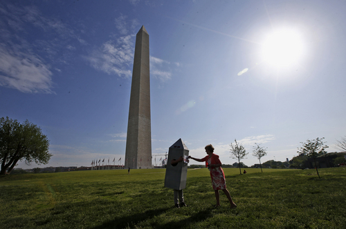Vicki Dixon, an Interior Department employee, right, helps her colleague Steven Avila, with his Washington Monument costume at the Washington Monument in Washington, Monday, May 12, 2014, ahead of a ceremony to celebrate its re-opening. The monument, which sustained damage from an earthquake in August 2011, is reopening to the public today. Avila made the costume to show his support for the re-opening of the monument. (AP Photo)