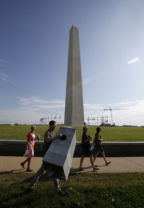 Steven Avila, an Interior Department employee, carries a Washington Monument costume as he arrives at the Washington Monument in Washington, Monday, May 12, 2014, ahead of a ceremony to celebrate its re-opening. The monument, which sustained damage from an earthquake in August 2011, is reopening to the public today. Avila made the costume to show his support for the re-opening of the monument. (AP Photo)