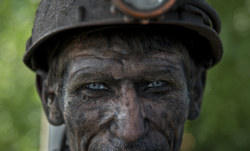 An Ukrainian coal miner waits for a bus after finishing his shift at a coal mine outside Donetsk, Ukraine, Tuesday, May 20, 2014. While steel workers in Mariupol joined anti-separatist actions supported by the management of the plants, miners refused to take part in a planned protest against the Donetsk People's Republic. (AP Photo/Vadim Ghirda)