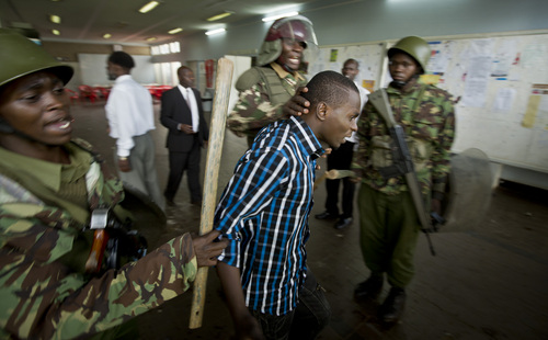 A Kenyan student is detained by riot police after surrendering in order to escape from a tear-gas-filled building inside Nairobi University's main campus in downtown Nairobi, Kenya Tuesday, May 20, 2014. Kenyan university students on Tuesday carried out demonstrations over a proposed increase in student fees, but the protests quickly turned into hours of running battles between students throwing rocks and security forces firing tear gas, before riot police chased the students inside their campus and cornered them in a building into which they fired dozens of tear gas grenades and for a while prevented anyone from leaving. (AP Photo/Ben Curtis)