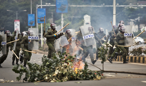Riot police charge past a burning barricade as they engage in running battles with protesting Kenyan students on the highway next to Nairobi University's main campus in downtown Nairobi, Kenya Tuesday, May 20, 2014. Kenyan university students on Tuesday carried out demonstrations over a proposed increase in student fees, but the protests quickly turned into hours of running battles between students throwing rocks and security forces firing tear gas, before riot police chased the students inside their campus and cornered them in a building into which they fired dozens of tear gas grenades and for a while prevented anyone from leaving. (AP Photo/Ben Curtis)