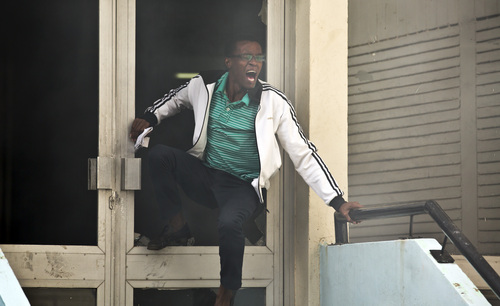 A student or member of university staff tries to escape from a tear-gas-filled building, before being chased back inside by riot police, inside Nairobi University's main campus in downtown Nairobi, Kenya,  Tuesday, May 20, 2014. Kenyan university students on Tuesday carried out demonstrations over a proposed increase in student fees, but the protests quickly turned into hours of running battles between students throwing rocks and security forces firing tear gas, before riot police chased the students inside their campus and cornered them in a building into which they fired dozens of tear gas grenades and for a while prevented anyone from leaving. (AP Photo/Ben Curtis)