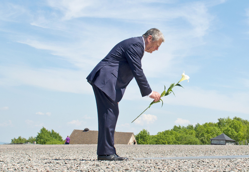 German President Joachim Gauck lays down a flower at a plain metal plaque during his visit at the former Nazi concentration camp Buchenwald near Weimar, Germany, Tuesday, May 20, 2014. (AP Photo/Jens Meyer)