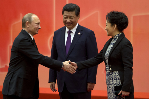 Russian President Vladimir Putin, left, shakes hands with Chinese first lady Peng Liyuan as Chinese President Xi Jinping looks on before a group photo for the fourth summit of the Conference on Interaction and Confidence Building Measures in Asia (CICA) in Shanghai, China, Tuesday, May 20, 2014. Putin met with Xi in a diplomatic boost for the isolated Russian leader but the two sides had yet to agree on a widely anticipated multibillion-dollar natural gas sale. (AP Photo/Ng Han Guan, Pool)