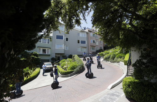 A group goes down Lombard Street on segways on Tuesday, May 20, 2014, in San Francisco.  San Francisco's crooked street could soon be closed to tourists in the summertime. A transportation commission is scheduled to consider an experimental shutdown of the famously curvaceous block of Lombard Street plus an adjoining block where cars line up and wait.(AP Photo/Marcio Jose Sanchez)