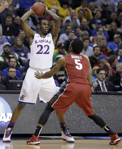 Kansas' Andrew Wiggins, left, looks to pass around Stanford's Chasson Randle during the first half of a third-round game of the NCAA college basketball tournament Sunday, March 23, 2014, in St. Louis. (AP Photo/Jeff Roberson)