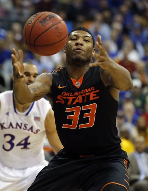 FILE - In this March 13, 2014 file photo, Oklahoma State guard Marcus Smart (33) reaches for the ball during the second half of an NCAA college basketball game against Kansas in the quarterfinals of the Big 12 Conference men's tournament in Kansas City, Mo.  Oklahoma State (21-12), the No. 9 seed in the West Region, will play No. 8 seed Gonzaga (28-6) Friday, March 21, 2014, in San Diego in its NCAA tournament opener. This will be SmartÌs last shot at tournament success because he will enter the NBA Draft after this season.(AP Photo/Orlin Wagner, File)