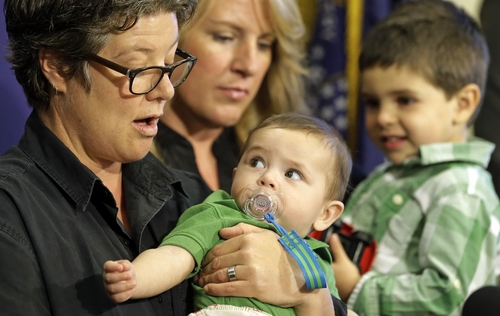 Kathy Harbin, left, and her spouse Michelle Call hold their children Louis Harbin-Call, 6 months, and Leo Harbin-Call, 2, as they speak during a news conference Friday, Feb. 28, 2014, at the Utah State Capitol, in Salt Lake City. Utah officials say in a new court filing that they have no choice but to put a freeze on granting benefits to newly married gay couples until a federal appeals court rules on the state's same-sex marriage ban. Parents affected by the announcement, along with their attorneys, spoke during the news conference. A federal judge in Utah ruled on May 19 that the state must recognize marriages that were legally performed in the window before a stay was issued. (AP Photo/Rick Bowmer)