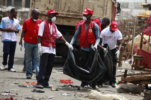 Red Cross personnel search for body parts at the site of one of Tuesday's car bomb in Jos, Nigeria, Wednesday, May 21, 2014. Two car bombs exploded at a bustling bus terminal and market the central Nigeria city, killing at least 118 people, wounding dozens and leaving bloodied bodies amid the flaming debris. (AP Photo/Sunday Alamba)