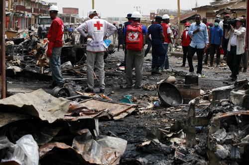 Red Cross personnel search for remains at the site of one of Tuesday's car bomb in Jos, Nigeria, Wednesday, May 21, 2014. Two car bombs exploded at a bustling bus terminal and market in Nigeria's central city of Jos on Tuesday, killing over 100 people, wounding dozens and leaving bloodied bodies amid the flaming debris. There was no immediate claim of responsibility for the twin car bombs. (AP Photo/Sunday Alamba)
