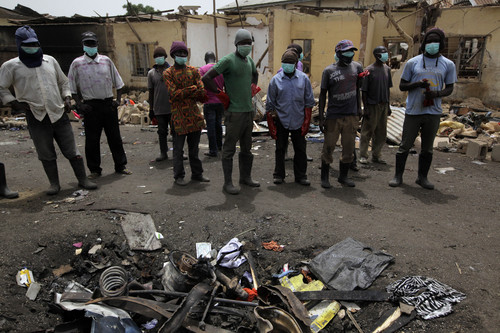 Rescue workers gather at the site of Tuesday's car bombs in Jos, Nigeria, Wednesday, May 21, 2014. Two car bombs exploded at a bustling bus terminal and market in Nigeria's central city of Jos on Tuesday, killing over 100 people, wounding dozens and leaving bloodied bodies amid the flaming debris. There was no immediate claim of responsibility for the twin car bombs.  (AP Photo/Sunday Alamba)