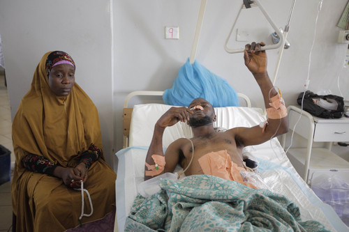 A relative sits with an unidentified victim of Tuesdays car bomb explosions in Jos University Teaching Hospital in  Jos, Nigeria, Wednesday, May 21, 2014. Two car bombs exploded at a bustling bus terminal and market in Nigeria's central city of Jos on Tuesday, killing over 100 people, wounding dozens and leaving bloodied bodies amid the flaming debris. There was no immediate claim of responsibility for the twin car bombs. (AP Photo/Sunday Alamba)