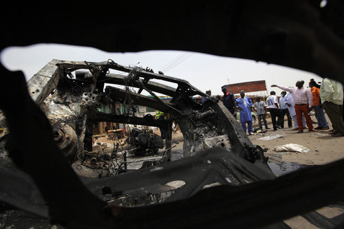 People inspect the remains of Tuesday's car bomb in Jos, Nigeria, Wednesday, May 21, 2014. Two car bombs exploded at a bustling bus terminal and market in Nigeria's central city of Jos on Tuesday, killing over 100 people, wounding dozens and leaving bloodied bodies amid the flaming debris. There was no immediate claim of responsibility for the twin car bombs. But they bore the hallmarks of Boko Haram, the Islamic extremist group that abducted nearly 300 schoolgirls last month and has repeatedly targeted bus stations and other locations where large numbers of people gather in its campaign to impose Islamic law on Nigeria. The second blast came half an hour after the first, killing some of the rescue workers who had rushed to the scene, which was obscured by billows of black smoke. (AP Photo/Sunday Alamba)