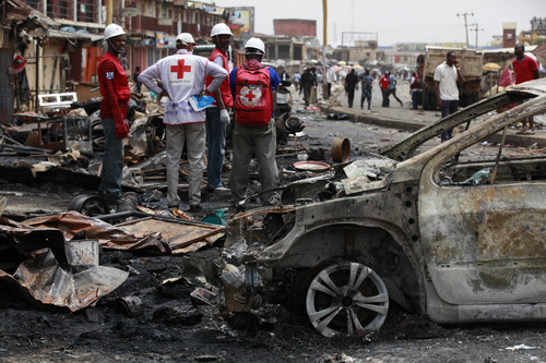 Red Cross personnel search for remains at the site of one of Tuesday's car bomb in Jos, Nigeria, Wednesday, May 21, 2014. Two car bombs exploded at a bustling bus terminal and market in Nigeria's central city of Jos on Tuesday, killing over 100 people, wounding dozens and leaving bloodied bodies amid the flaming debris. There was no immediate claim of responsibility for the twin car bombs. But they bore the hallmarks of Boko Haram, the Islamic extremist group that abducted nearly 300 schoolgirls last month and has repeatedly targeted bus stations and other locations where large numbers of people gather in its campaign to impose Islamic law on Nigeria. The second blast came half an hour after the first, killing some of the rescue workers who had rushed to the scene, which was obscured by billows of black smoke. (AP Photo/Sunday Alamba)