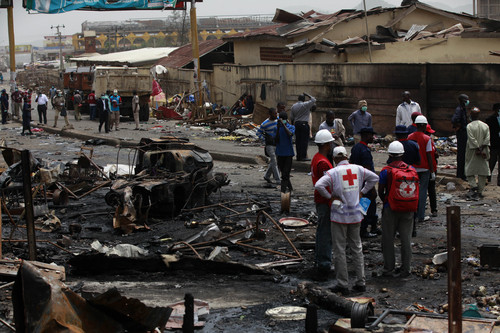 People gather at the site of one of Tuesday's car bombs in Jos, Nigeria, Wednesday, May 21, 2014. Two car bombs exploded at a bustling bus terminal and market in Nigeria's central city of Jos on Tuesday, killing over 100 people, wounding dozens and leaving bloodied bodies amid the flaming debris. There was no immediate claim of responsibility for the twin car bombs. But they bore the hallmarks of Boko Haram, the Islamic extremist group that abducted nearly 300 schoolgirls last month and has repeatedly targeted bus stations and other locations where large numbers of people gather in its campaign to impose Islamic law on Nigeria. The second blast came half an hour after the first, killing some of the rescue workers who had rushed to the scene, which was obscured by billows of black smoke. (AP Photo/Sunday Alamba)
