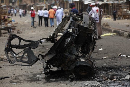 People walk past the remains of one of Tuesday's car bombs in Jos, Nigeria, Wednesday, May 21, 2014. Two car bombs exploded at a bustling bus terminal and market in Nigeria's central city of Jos on Tuesday, killing over 100 people, wounding dozens and leaving bloodied bodies amid the flaming debris. There was no immediate claim of responsibility for the twin car bombs. But they bore the hallmarks of Boko Haram, the Islamic extremist group that abducted nearly 300 schoolgirls last month and has repeatedly targeted bus stations and other locations where large numbers of people gather in its campaign to impose Islamic law on Nigeria. The second blast came half an hour after the first, killing some of the rescue workers who had rushed to the scene, which was obscured by billows of black smoke. (AP Photo/Sunday Alamba)