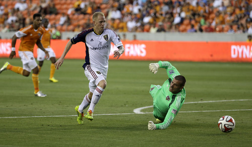 Real Salt Lake's Luke Mulholland, left, gets past Houston Dynamo goalkeeper Tally Hall, right, to score a goal during the second half of a MLS soccer game Sunday, May 11, 2014, in Houston. Real Salt Lake won 5-2. (AP Photo/David J. Phillip)